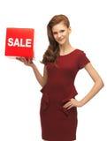 Adolescente en vestido rojo con la muestra de la venta Fotos de archivo libres de regalías