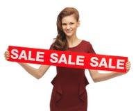 Adolescente en vestido rojo con la muestra de la venta Fotografía de archivo