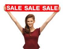 Adolescente en vestido rojo con la muestra de la venta Imagenes de archivo