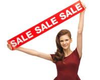 Adolescente en vestido rojo con la muestra de la venta Fotos de archivo