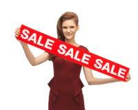 Adolescente en vestido rojo con la muestra de la venta Imagen de archivo libre de regalías