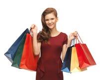 Adolescente en vestido rojo con los panieres Foto de archivo libre de regalías