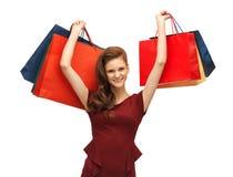 Adolescente en vestido rojo con los panieres Imagenes de archivo