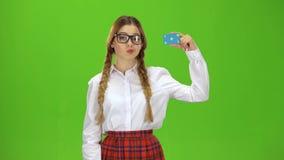Adolescente en vidrios aumenta una tarjeta y muestra una autorización Pantalla verde metrajes