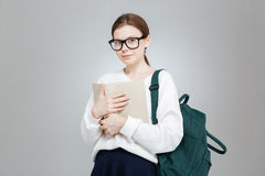 Adolescente en vidrios con la mochila que coloca y que sostiene el libro Imagenes de archivo