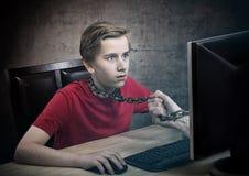 Adolescente encadenado a su ordenador Fotografía de archivo