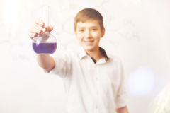 Adolescente encantado positivo que sostiene el frasco con el reactivo Imagen de archivo