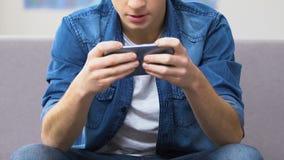 Adolescente encantado que juega al videojuego rápido en el smartphone, tiempo libre metrajes