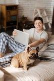 Adolescente encantado que presenta en cámara con su animal doméstico Imagen de archivo