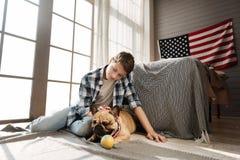 Adolescente encantado que se sienta cerca de su mejor amigo canino Foto de archivo libre de regalías