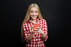 Adolescente encantado que usa smartphone contra fondo negro Imágenes de archivo libres de regalías