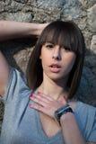 Adolescente encantador en la presentación casual contra una pared de la roca Fotografía de archivo