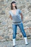 Adolescente encantador en la presentación casual contra una pared de la roca Imagen de archivo