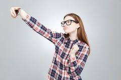 Adolescente encantador en los vidrios que toman el selfie con el teléfono celular Imágenes de archivo libres de regalías