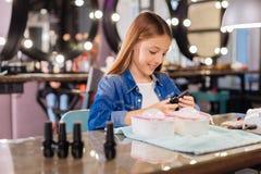 Adolescente encantador que escudriña la botella del esmalte de uñas Fotografía de archivo libre de regalías