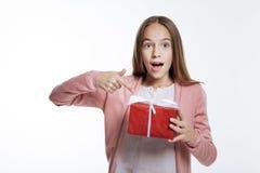 Adolescente encantador que señala en la caja de regalo con su finger Foto de archivo libre de regalías