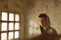 Adolescente encapuchado en una casa abandonada Foto de archivo