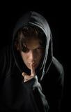 Adolescente encapuchado tiene un secreto en fondo negro Imagen de archivo libre de regalías