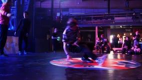 Adolescente energético atrativo no t-shirt com as listras que breakdancing na fase video estoque