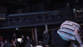 Adolescente energético bonito no t-shirt com as listras que breakdancing na fase filme