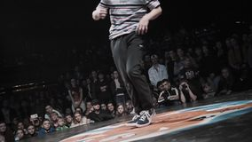 Adolescente energético bonito no t-shirt com as listras que breakdancing na fase video estoque