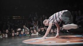 Adolescente energético caucasiano no t-shirt com as listras que breakdancing na fase video estoque