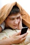 Adolescente enfadado con el teléfono móvil Foto de archivo
