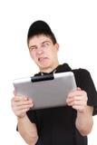 Adolescente enfadado con la tableta Foto de archivo libre de regalías