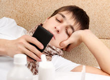 Adolescente enfermo con el teléfono móvil Imágenes de archivo libres de regalías