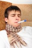 Adolescente enfermo con el termómetro Fotos de archivo