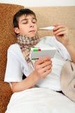 Adolescente enfermo con el termómetro Imagenes de archivo