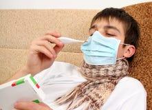 Adolescente enfermo con el termómetro Fotos de archivo libres de regalías
