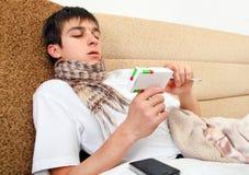 Adolescente enfermo con la caja de la droga Imágenes de archivo libres de regalías