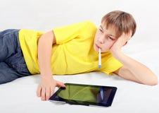 Adolescente enfermo con la tableta Imagenes de archivo