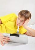 Adolescente enfermo con la tableta Fotografía de archivo