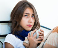 Adolescente enfermo con té y la medicación calientes dentro Imagen de archivo