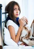 Adolescente enfermo con té y la medicación calientes dentro Imagenes de archivo