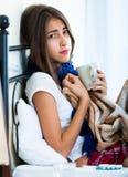 Adolescente enfermo con té y la medicación calientes dentro Fotografía de archivo