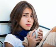 Adolescente enfermo con té y la medicación calientes dentro Fotografía de archivo libre de regalías