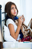 Adolescente enfermo con té y la medicación calientes dentro Imagen de archivo libre de regalías