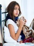 Adolescente enfermo con té y la medicación calientes dentro Foto de archivo libre de regalías
