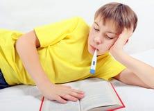 Adolescente enfermo con un libro Foto de archivo