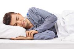 Adolescente enfermo con un termómetro en su boca que miente en cama Fotos de archivo libres de regalías
