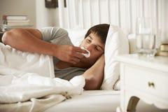Adolescente enfermo en cama en casa Foto de archivo libre de regalías
