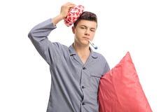 Adolescente enfermo en los pijamas que llevan a cabo un icepack en su cabeza y a Imagenes de archivo