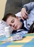 Adolescente enfermo que duerme con las p?ldoras Foto de archivo libre de regalías