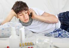 Adolescente enfermo que invita al teléfono móvil Fotografía de archivo libre de regalías