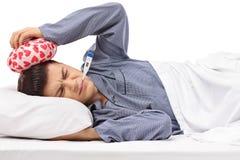 Adolescente enfermo que miente en la cama que lleva a cabo un icepack en su cabeza y a Fotografía de archivo libre de regalías