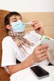 Adolescente enfermo que mira en la caja de la droga Fotos de archivo