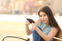 Adolescente engraçado que joga jogos em um telefone esperto Fotografia de Stock